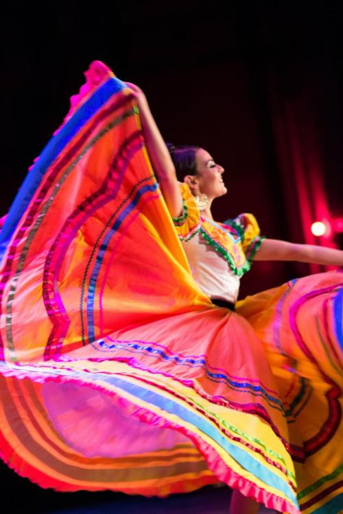 A solo dancer from Calidanza is shown wearing a traditional Michoacan dress that is vibrantly colored.  She is smiling and holding up one edge of the dress.