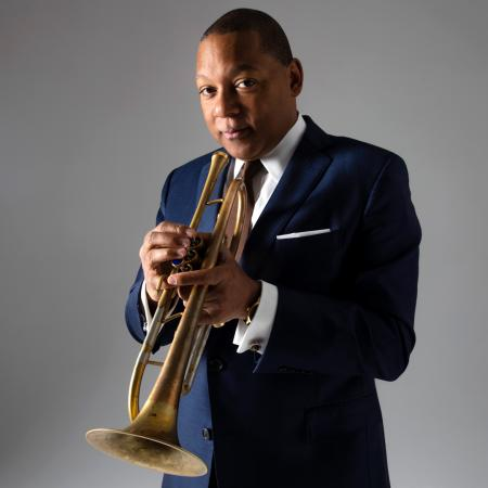 Wynton Marsalis is looking into the camera while holding his trumpet.