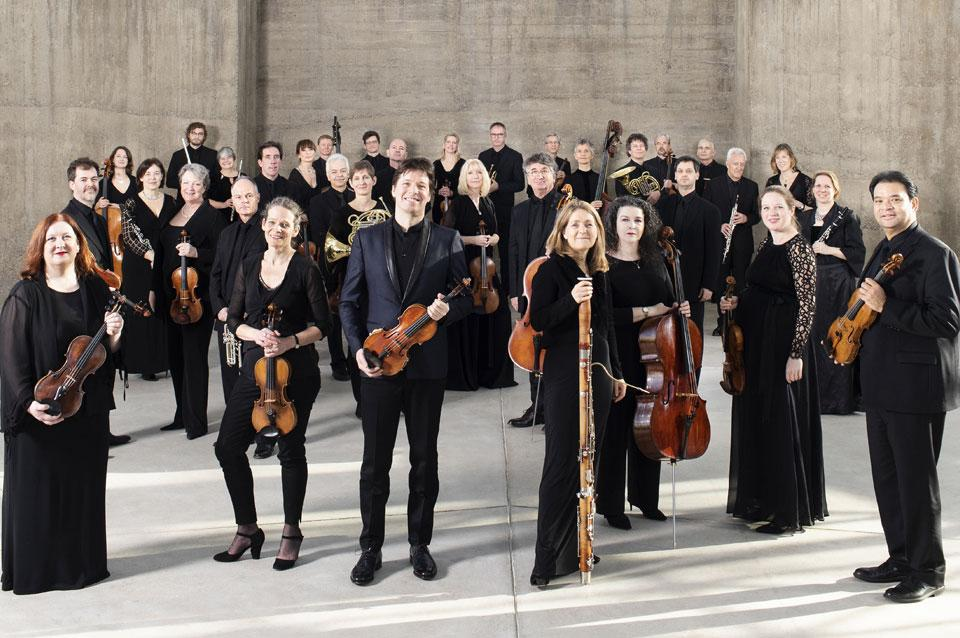 Academy of St. Martin in the Fields pose in neat rows with their instruments, looking directly at the camera.