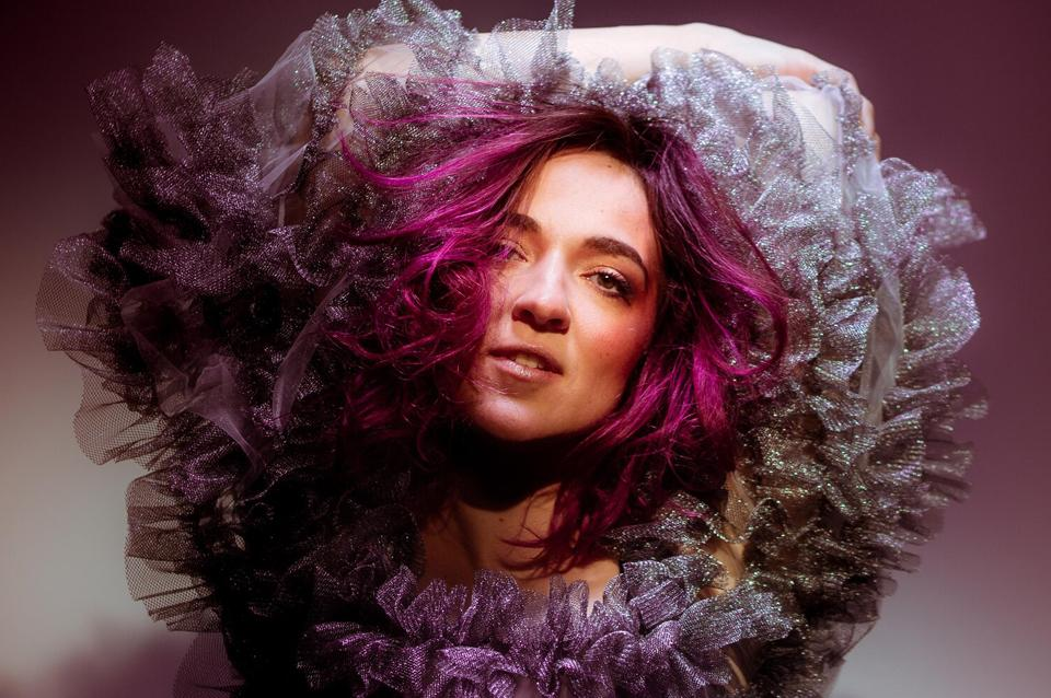 Becca Stevens with pink hair and a purple tulle top