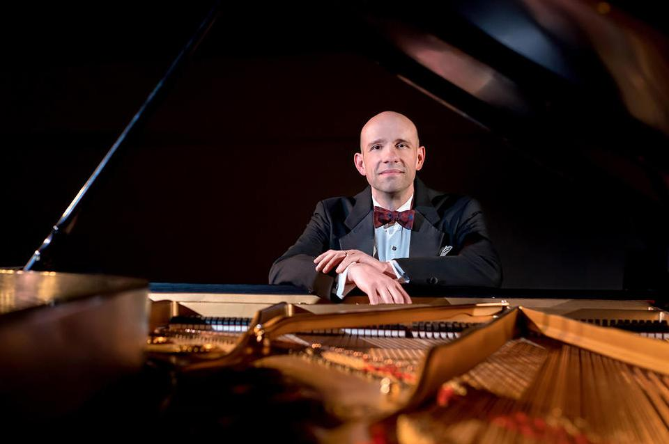 Christopher Taylor plays piano wearing a black suit and red bowtie.