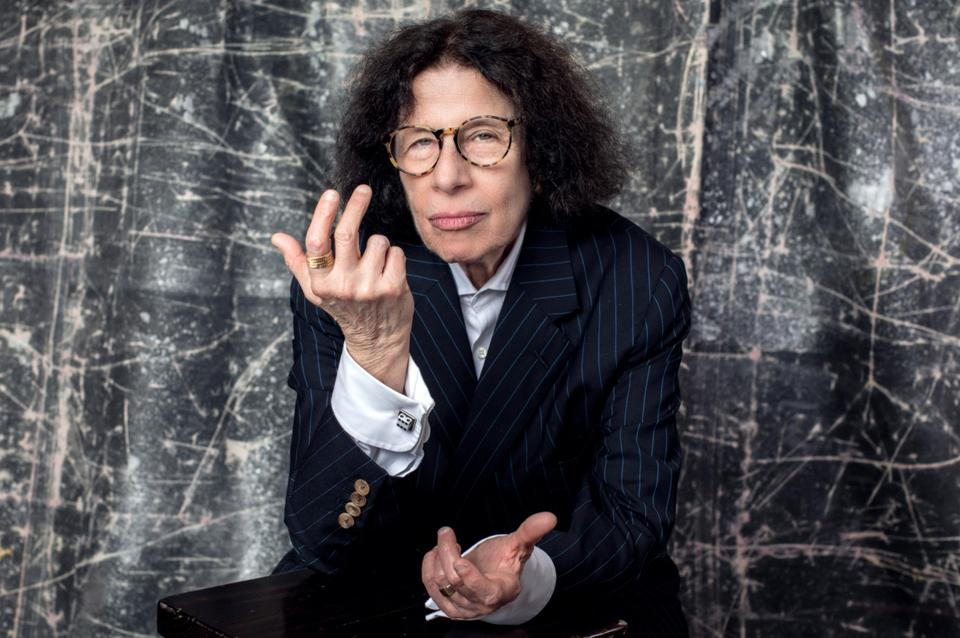 Fran Lebowitz poses in front of a gray backrop looking directly at the camera.