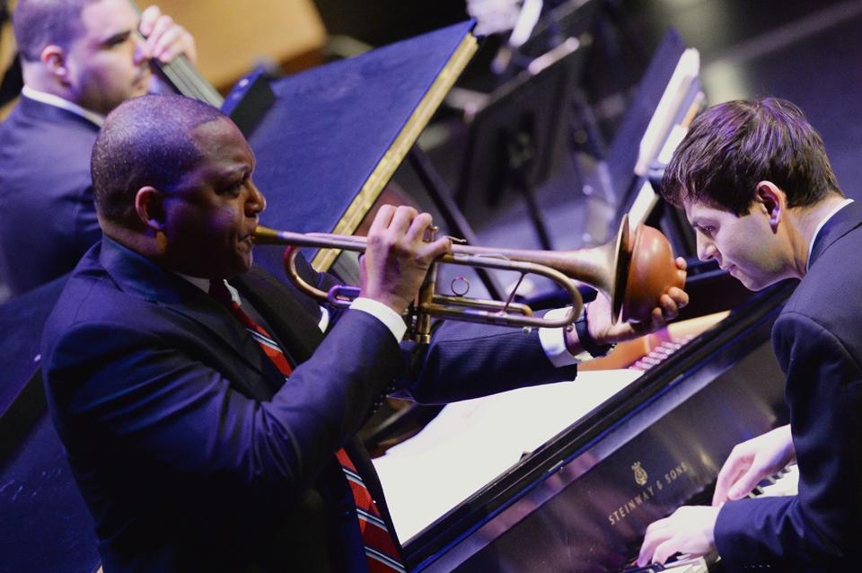 Members of Jazz at Lincoln Center Orchestra play their instruments on stage.