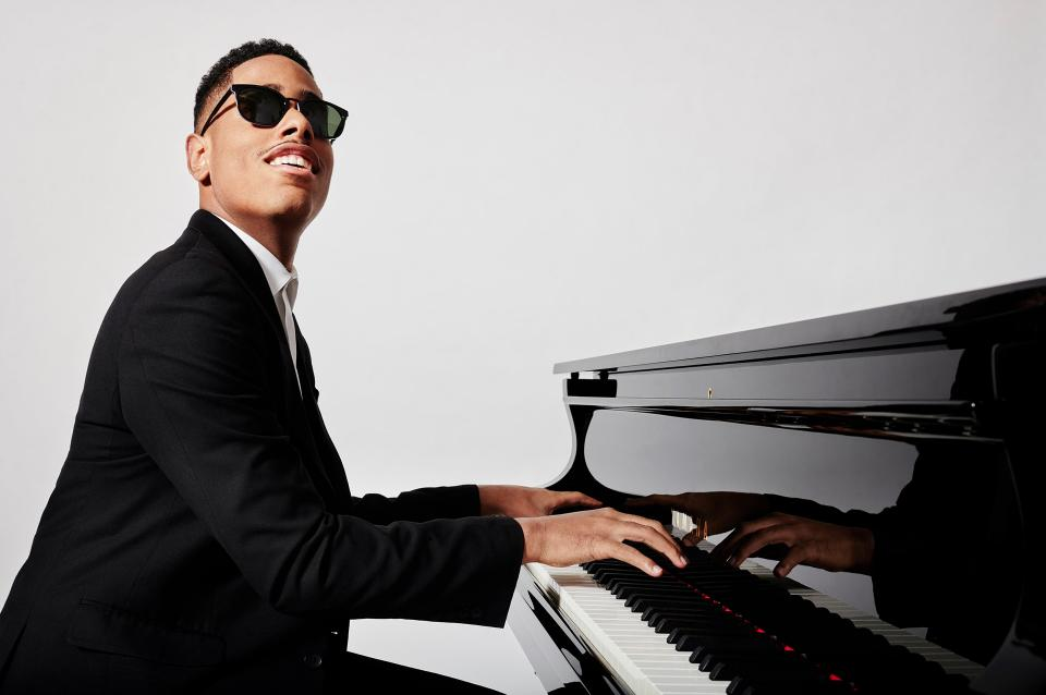Matthew Whittaker playing the piano and smiling.