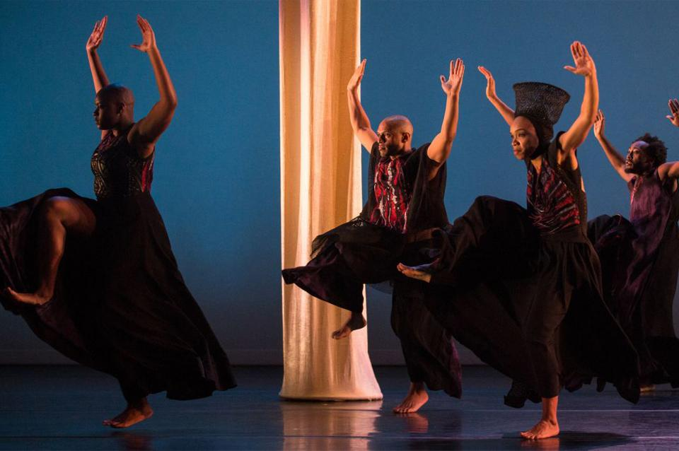 Four dancers wearing all black dance on stage.