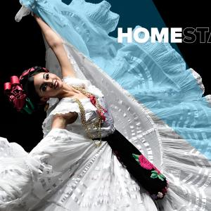 A Ballet Folklórico dancer in a white & blue dress is arching her back and lifting up the hem of her dress.