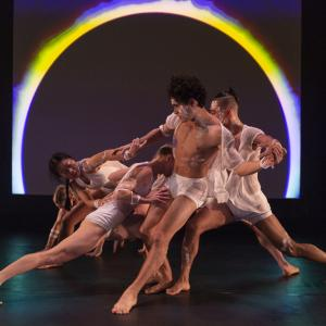 Five dancers entangled with outstretched arms and legs