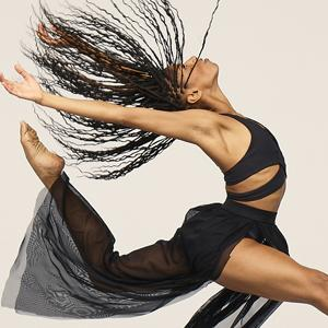 Black-clad female Ailey dancer leaping with braided long hair trailing behind