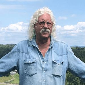 Arlo Guthrie in a chambray shirt standing in field with arms outstretched