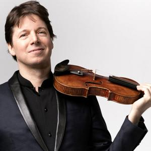 Joshua Bell poses with his instrument, looking directly at the camera.