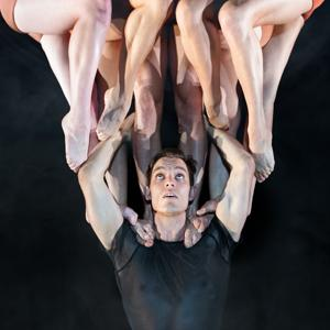 A man looks directly above him at a few pairs of legs, as he balances them on his shoulders.