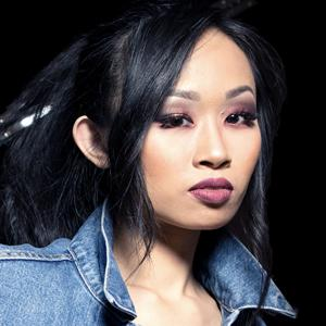 Headshot of pianist Connie Han with hair up, wearing a denim shirt with the collar up