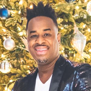 Damien Sneed sitting in front of a Christmas tree.