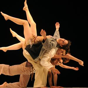 Four dancers grouped closely together with bodies arrayed horizontally