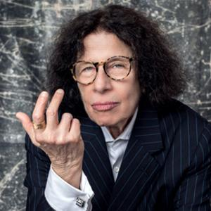 Fran Lebowitz poses in front of a gray backdrop looking directly at the camera.
