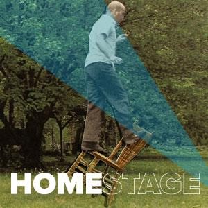 Jeremy Rourke is standing on top of a chair that is balancing on a chair that is balancing on its rear legs. - ` HomeStage'