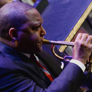 Bandleader Wynton Marsalis  in a navy suit and red tie blowing his trumpet