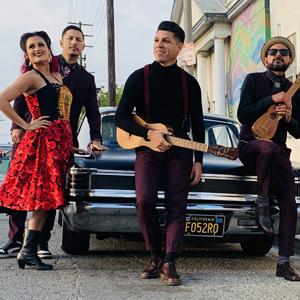 Group photo of Las Cafeteras posing with instruments in front of black classic car