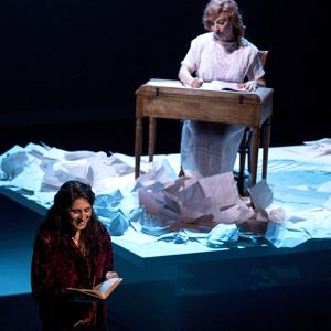 Liz Queler reads a book on stage and a woman wearing a white dress sits by a desk behind Liz Queler.