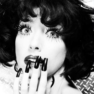 Black and white portrait of Meow Meow with hand to her face showing long painted nails