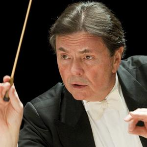 Close-up of Gerard Schwartz in a black tuxedo conducting with baton.