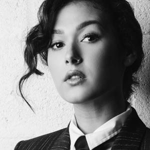 Black and white portrait of Nella with her hair up, wearing a suit and tie