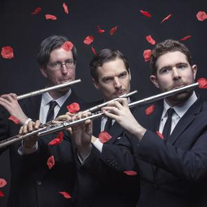 Three men wearing suits and playing flutes with red rose petals  falling on them.