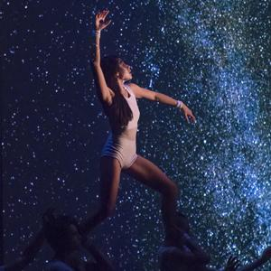 A standing female dancer in a beige leotard held up by two other dancers in front of a starry backdrop