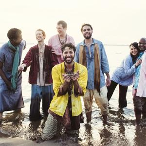 Group photo of six men and one woman, smiling and standing in water wearing loose, pastel clothing