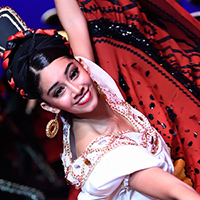 Female Mexican folkloric  dancer smiling while spinning in red skirt