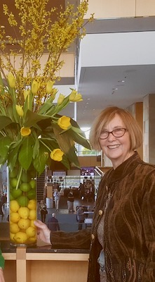 Photo shows Denise Verbeck standing next to a large bouquet of flowers just outside the Bartholomew Room.